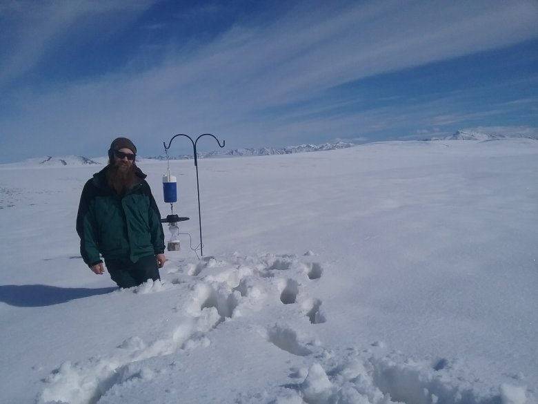 Field technician standing in snow next to a carbon dioxide light trap.